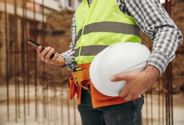 Onherkenbaar mannelijke bouwer met helm mobiele telefoon browsen tijdens pauze in het werk op de bouwplaats