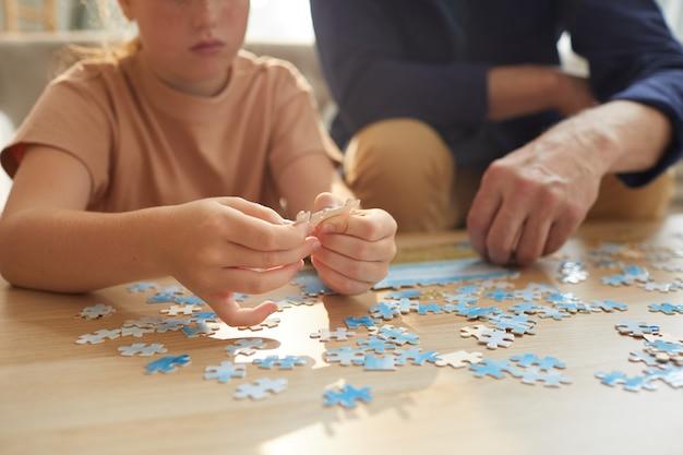 Onherkenbaar meisje bordspellen spelen met grootouders terwijl ze samen genieten van tijd
