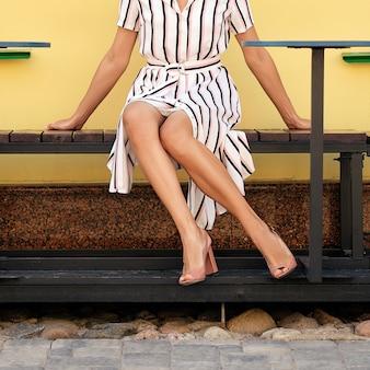 Onherkenbaar meisje in lange jurk zittend op een bankje tussen de tafels op het terras van het café