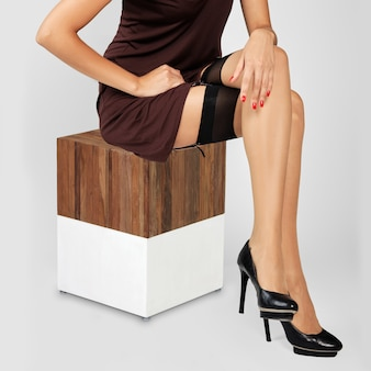 Onherkenbaar meisje met lang krullend haar, zittend in korte jurk en kousen met kousenband