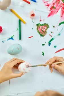 Onherkenbaar meisje schilderen, tekenen met penseel eieren thuis. kind dat zich voorbereidt op pasen, plezier heeft en feest viert. vrolijk pasen, diy