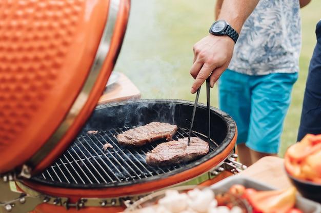Onherkenbaar mensen kokend vlees bij de grill.