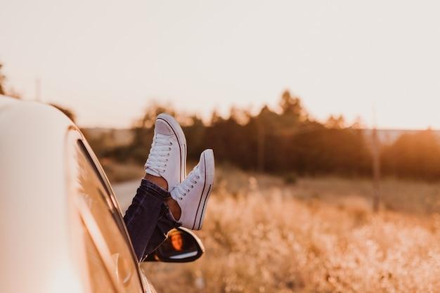 Onherkenbaar modern hipster meisje ontspannen in een auto. voeten buiten het raam bij zonsondergang. reizen concept