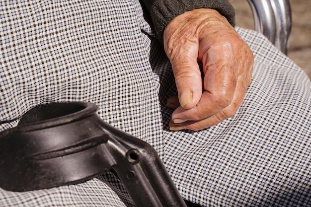 Onherkenbaar oude vrouw zitten met behulp van een kruk. ouderen gehandicapte levensstijl. verpleeghuisconcept voor pensioneringsmensen. geriatrisch huis voor ouderenzorg.