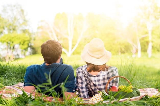 Onherkenbaar paar die op plaid in bos liggen