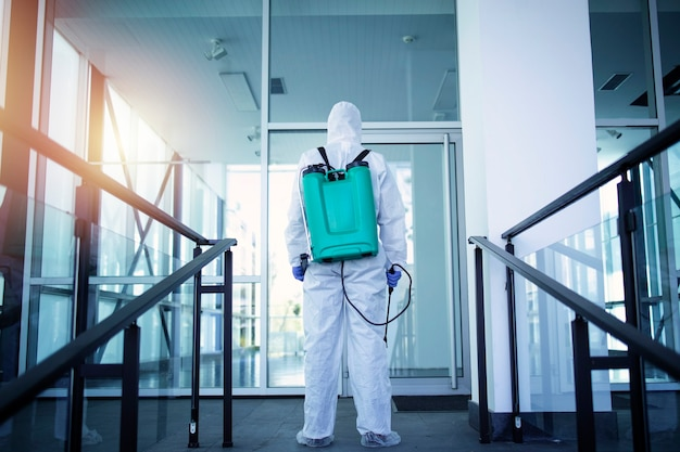 Onherkenbaar persoon in wit beschermend pak die openbare ruimtes desinfecteert om de verspreiding van het zeer besmettelijke coronavirus te stoppen