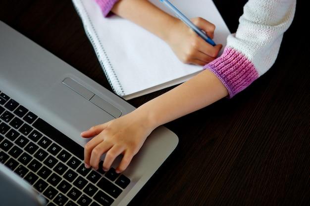 Onherkenbaar schoolmeisje dat thuis met een notitieboekje bestudeert en schoolhuiswerk doet. afstandsonderwijs online onderwijs.