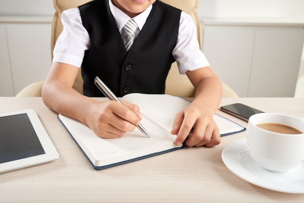 Onherkenbaar slim geklede jongenszitting bij bureau in bureau en het schrijven in dagboek