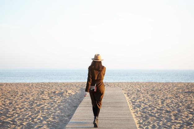 Onherkenbaar stijlvolle vrouw met hoed, lange jas en schoudertas wandelen langs promenade