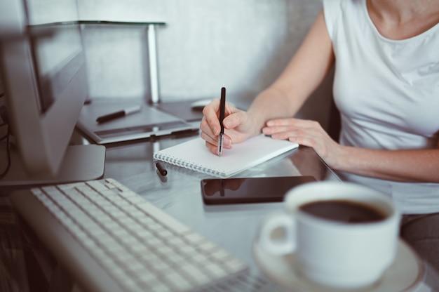 Onherkenbaar vrouw handen schrijven in lege notebook en computer. freelancer thuis met behulp van smartphone en laptop tijdens quarantaine. internetmarketing, financiën, zaken, concept op afstand