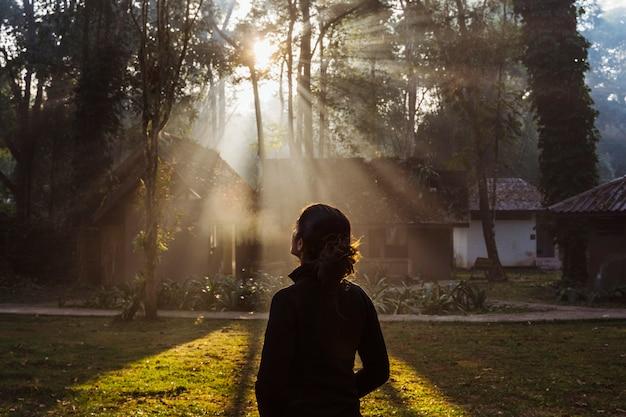 Onherkenbaar vrouw stond aan de voorkant van een geweldige zonsopgang in het bos. nationaal park in thailand met camping bungalows. natuur, trektochten en toerisme in azië. rustiek blokhuis in het bos.