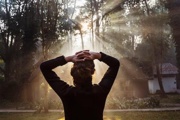 Onherkenbaar vrouw stond aan de voorkant van een geweldige zonsopgang in het bos. nationaal park in thailand. trekking en toerisme in azië. nieuwe ervaring in contact met de natuur. gezonde spirituele levensstijl.