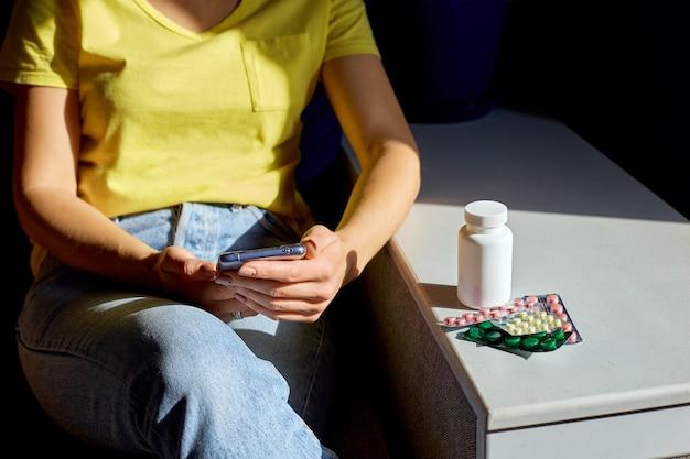 Onherkenbaar vrouw zittend op de bank met blisterverpakking van pillen met behulp van online apotheek winkel, apotheek kopen op internet