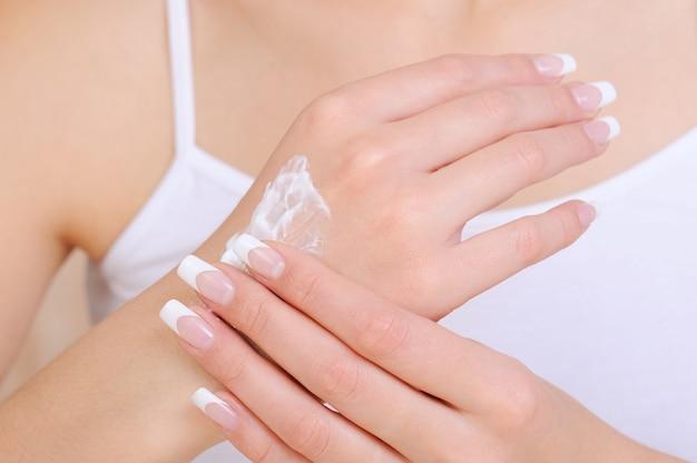 Onherkenbaar vrouwelijke persoon die cosmetische vochtinbrengende crème bij de hand toepast
