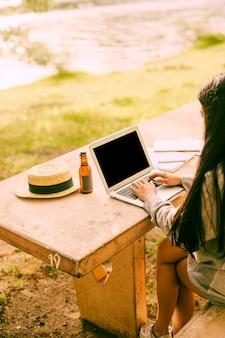 Onherkenbaar wijfje die laptop buiten dichtbij meer met behulp van