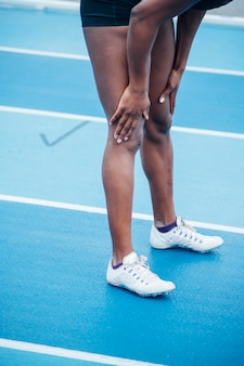 Onherkenbare afrosportvrouw in sportkleding die race begint vanuit gehurkte startpositie op startblokken