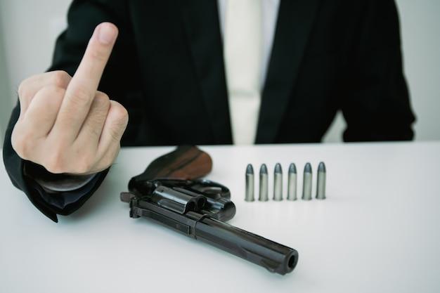 Onherkenbare agressieve aziatische zakenman trekt het pistool uit de pistoolhouder in zijn pak. zakenman of agent in zwart pak met het revolverpistool op tafel en middelvinger.