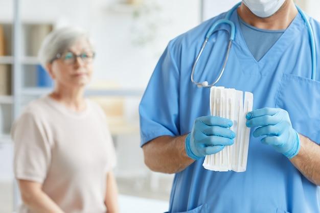Onherkenbare arts in blauw uniform en handschoenen die teststokje nemen voor hogere vrouwelijke patiënt die achter hem zit