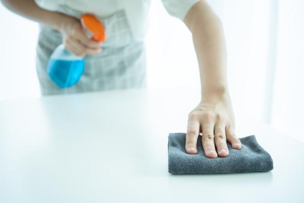 Onherkenbare aziatische huishoudster met behulp van microfiber vegen op een oppervlak van tafel close-up met copyspace. meid schoonmaken en ontsmetten op een vuile ondergrond.