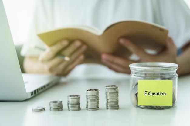 Onherkenbare aziatische jongeman die zijn geld in de spaarmand stopt, het concept van geld besparen voor onderwijs.