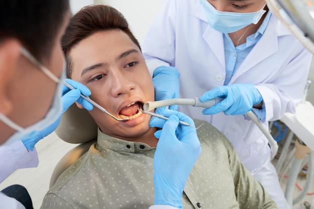 Onherkenbare aziatische tandarts en verpleegster die de tanden van de mannelijke patiënt onderzoeken