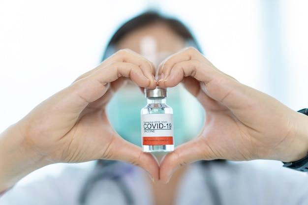 Onherkenbare aziatische vrouwelijke arts die het coronavirus 2019-ncov-geneesvaccin op een hand close-up toont. voltooid covid-19-vaccin klaar voor gebruik bij de mens.
