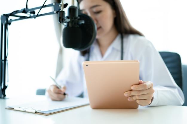 Onherkenbare aziatische vrouwelijke arts draagt een gezichtsmasker en geeft een consult aan de patiënt in het ziekenhuis. dokter tonen en wijzen op tablet, lege tablet met leeg scherm. gezondheidszorg en wellness-concept.