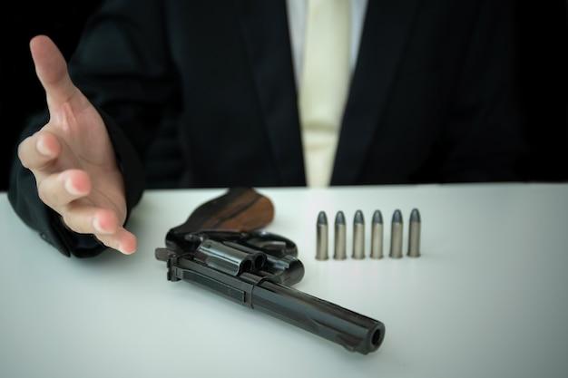 Onherkenbare aziatische zakenman trekt het pistool uit de pistoolhouder in zijn pak van dichtbij. zakenman of agent in zwart pak met het revolverpistool op tafel.