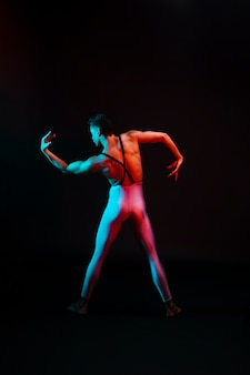 Onherkenbare balletdanser in turnpakje met gebogen armen in de schijnwerpers