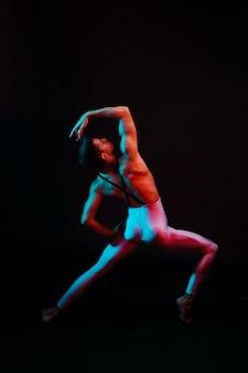 Onherkenbare balletdanser met gebogen benen uit elkaar in de schijnwerpers