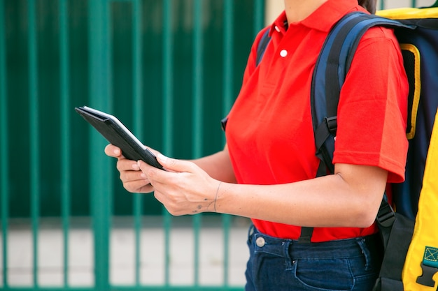 Onherkenbare bezorger die het vereiste adres op tablet bekijkt. vrouwelijke koerier in rood shirt met gele thermische rugzak die de bestelling te voet aflevert. voedselbezorgservice en online winkelconcept