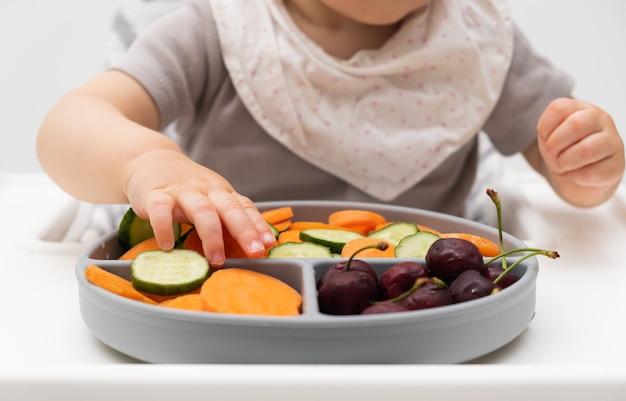 Onherkenbare blanke baby van ongeveer 1 jaar oud eten van siliconen bord met verse groenten fruit bessen zelfvoeding voor kinderen babyled speenidee gezonde voeding van vast voedsel voor baby's