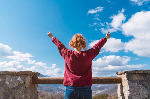 Onherkenbare blanke vrouw die met open armen naar het uitzicht kijkt. vrijheidsconcept.