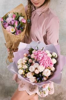 Onherkenbare bloemist toont boeketten van rozen- en tulpenbloemen. jonge vrouw met een roze boeket. bloemistenworkshop, vakmanschap, decor, klein bedrijf, cadeauconcept