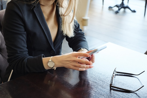 Onherkenbare blonde zakenvrouw in pak met telefoon zittend aan een tafel in een café, close-up