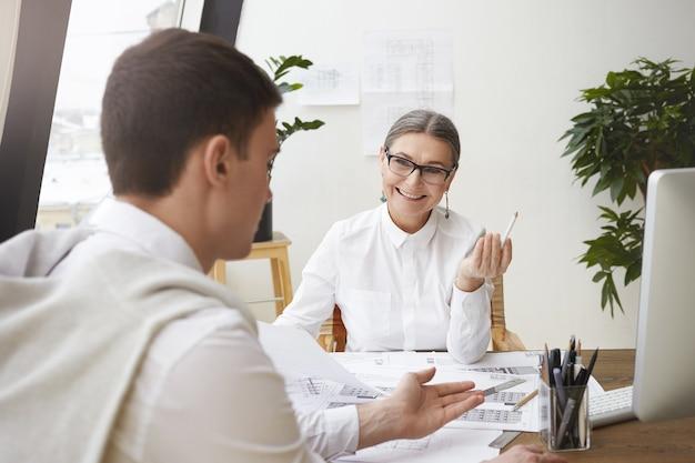 Onherkenbare brunette jonge mannelijke architect zittend aan een bureau met tekeningen terwijl hij iets bespreekt met zijn vrolijke volwassen vrouwelijke baas die naar hem lacht en zijn creatieve ideeën goedkeurt