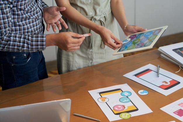 Onherkenbare collega's die tablet bekijken en verschillende pictogrammen proberen