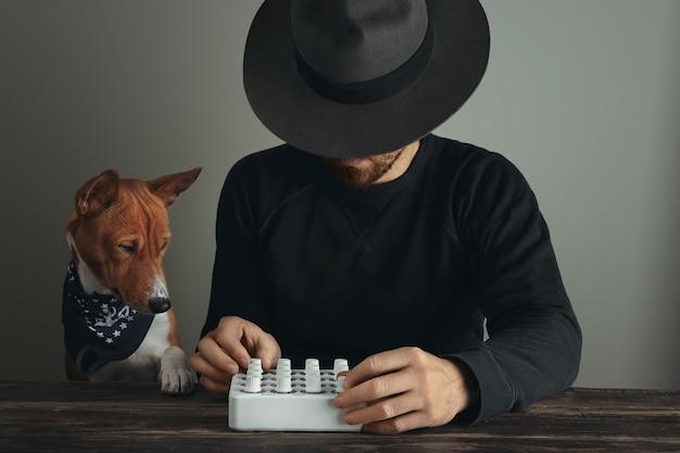 Onherkenbare creatieve muzikant in prachtige hoed met draaiknoppen op zijn midi mixer en nieuwsgierige hond