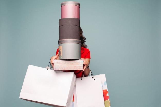 Onherkenbare dame met veel dozen en boodschappentassen uit winkelcentrum.