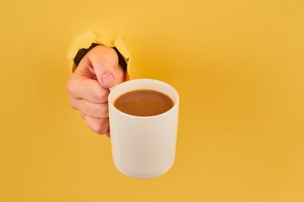 Onherkenbare de koffiemok van de persoonsholding op oranje close-up als achtergrond