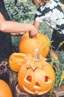 Onherkenbare dochter en moeder halen zaden en vezelachtig materiaal uit een pompoen