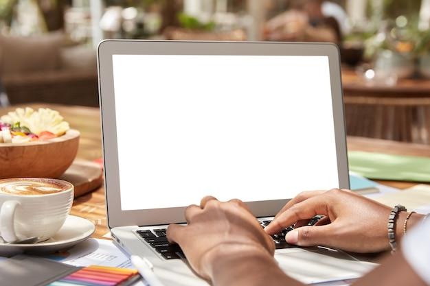 Onherkenbare donkere hipster student typt informatie op toetsenbord