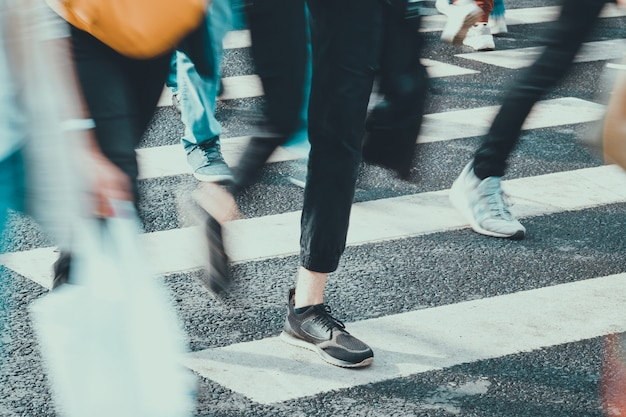 Onherkenbare en wazige mensen lopen in de zomer langs de voetgangersoversteekplaats in de stad.