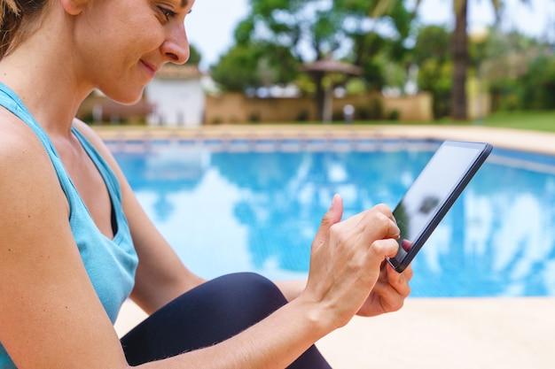 Onherkenbare fitnessvrouw die buiten een online sportles kiest. horizontaal zijaanzicht van een jonge vrouw die verbinding maakt met technologie naar een gymles met vrienden naast een zwembad.