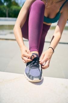 Onherkenbare fitte vrouw trekt haar sneakers aan voordat ze gaat trainen tijdens een selectieve focus in de zomerochtend