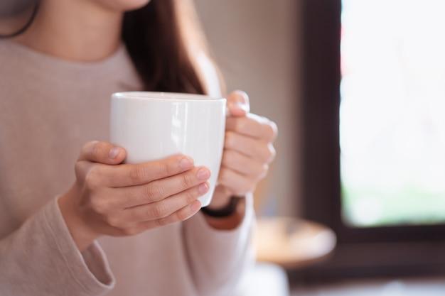 Onherkenbare gelukkige aziatische vrouw die een hete koffiemok in haar handen houdt