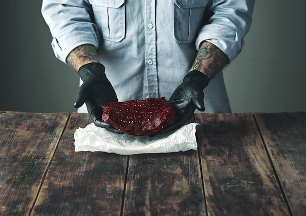 Onherkenbare getatoeëerde slager in zwarte handschoenen biedt een stuk luxe walvisvlees aan boven wit knutselpapier