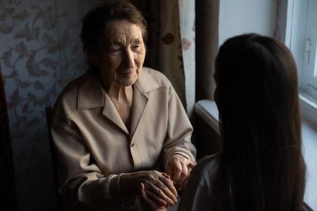 Onherkenbare grootmoeder en haar kleindochter hand in hand.