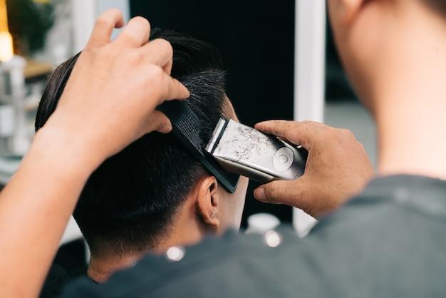 Onherkenbare haarstylist die het haar van de klant snijdt met trimmer en kam