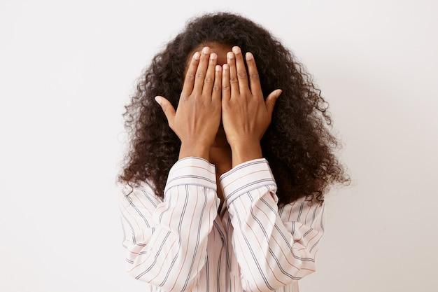 Onherkenbare jonge donkerhuidige vrouw met krullend afro-haar dat het gezicht met beide handen bedekt, haar gevoelens speelt of verbergt, bang is, een gestreept shirt draagt. lichaamstaal, reacties en emoties